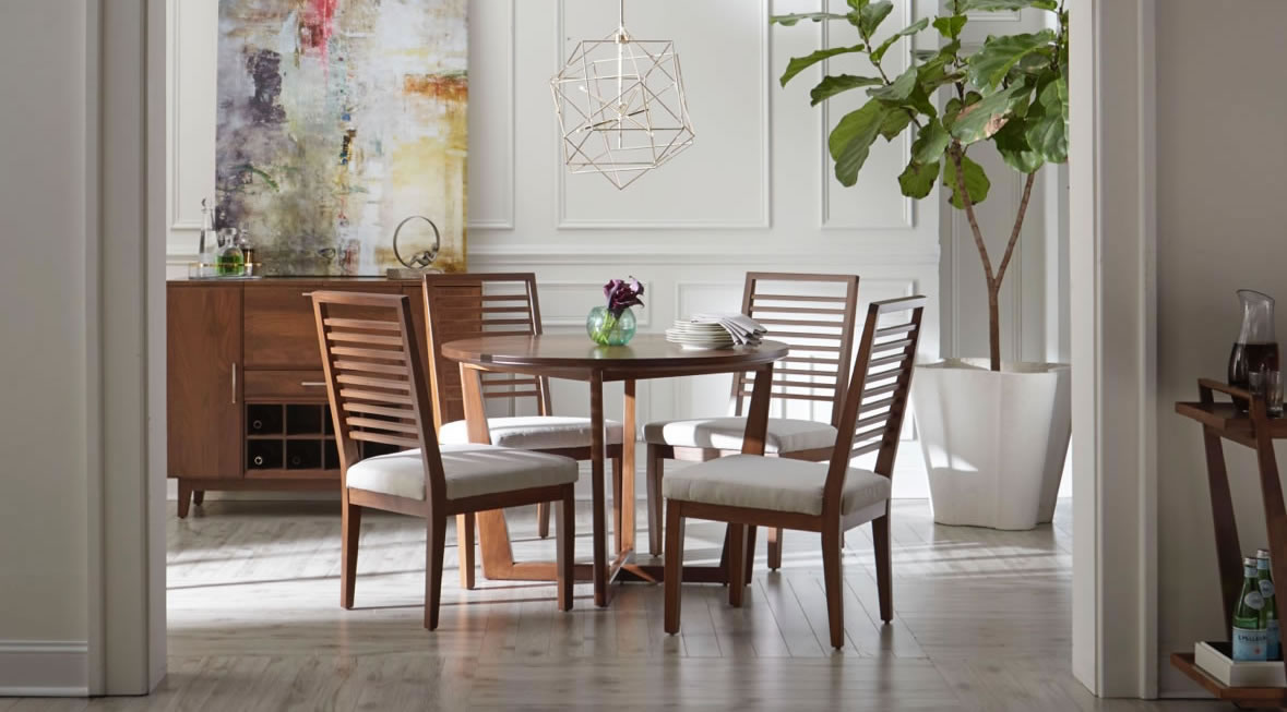 Circular wood dining table and four chairs with tight slats and white cushioned bottoms