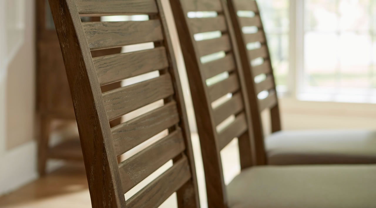 Close up of three slated backed chairs showing wood grain