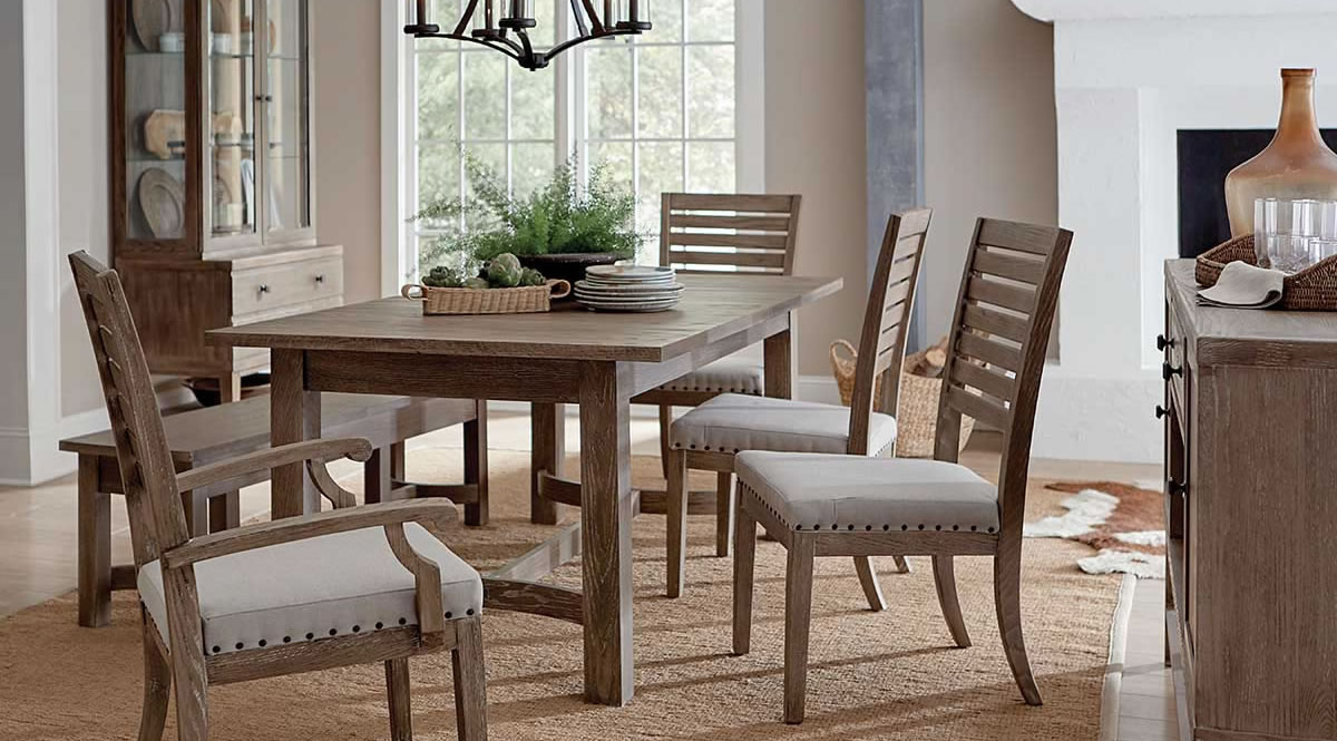 Farmhouse style rectangular dining table with four chairs and a bench and matching hutch in background